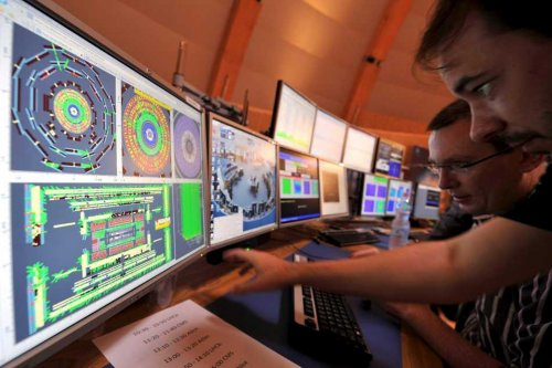 CERN LHC scientists at the Atlas controls, presumably hoping the darn operating system doesn't freeze up just when they inadvertently go over the danger mark in beam energy and plunge Geneva into darkness